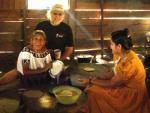 Mayan grandmother and daughter cooking tortillas with white bearded man hamming