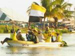 Small boat filled with colorfully dressed people holding plants, arms raised in