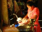 Young Mayan woman grinding corn with a hand grinder