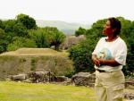 Mature Mayan woman standing in front of Mayan ruins